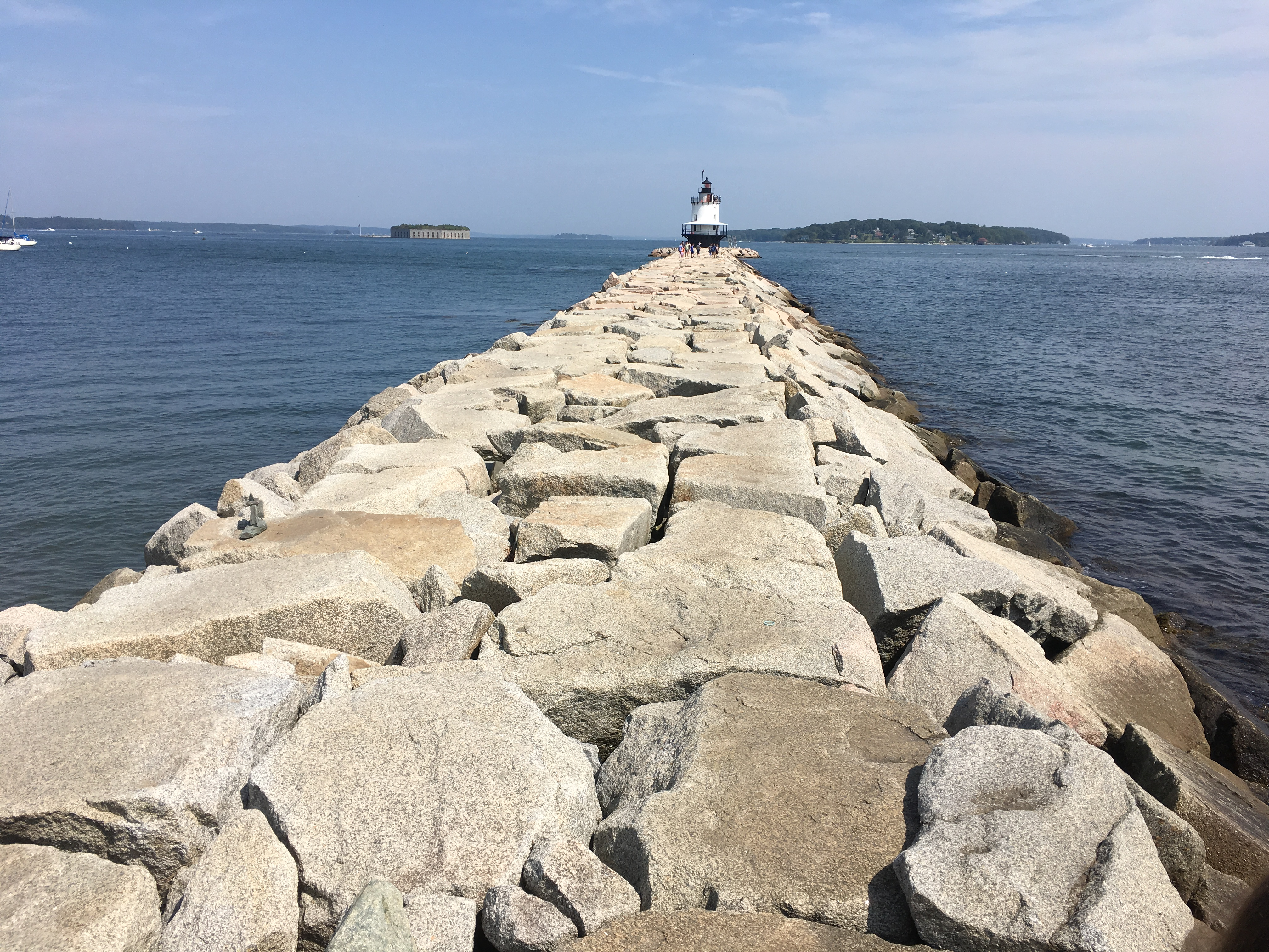 Rocky pier that leads to a lighthouse.